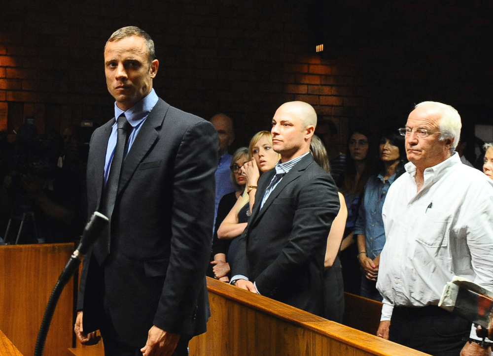 Description of . Olympian Oscar Pistorius, foreground, stands following his bail hearing, as his brother Carl, centre, and father Henke, right, look on,  in Pretoria, South Africa, Tuesday, Feb. 19, 2013. Pistorius fired into the door of a small bathroom where his girlfriend was cowering after a shouting match on Valentine's Day, hitting her three times, a South African prosecutor said Tuesday as he charged the sports icon with premeditated murder. The magistrate ruled that Pistorius faces the harshest bail requirements available in South African law. He did not elaborate before a break was called in the session.  (AP Photo-Masi Losi-Pretoria News)
