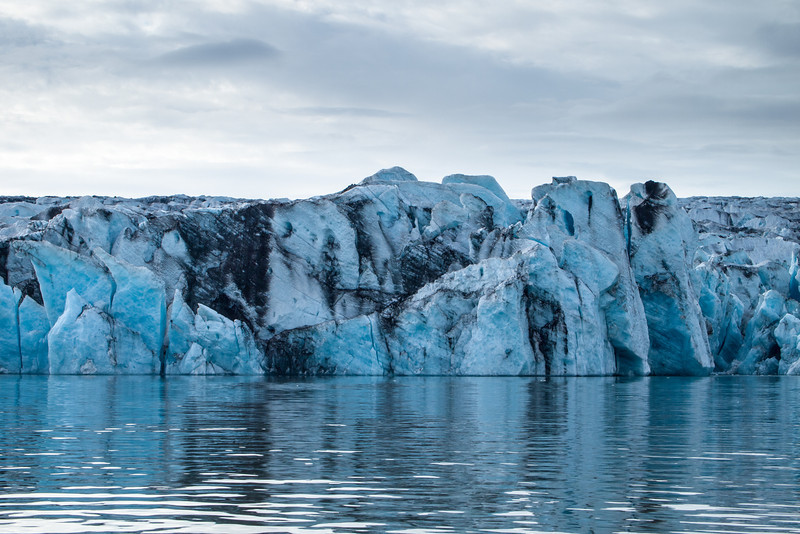 Base of the glacier. The black streaks are volcanic ash