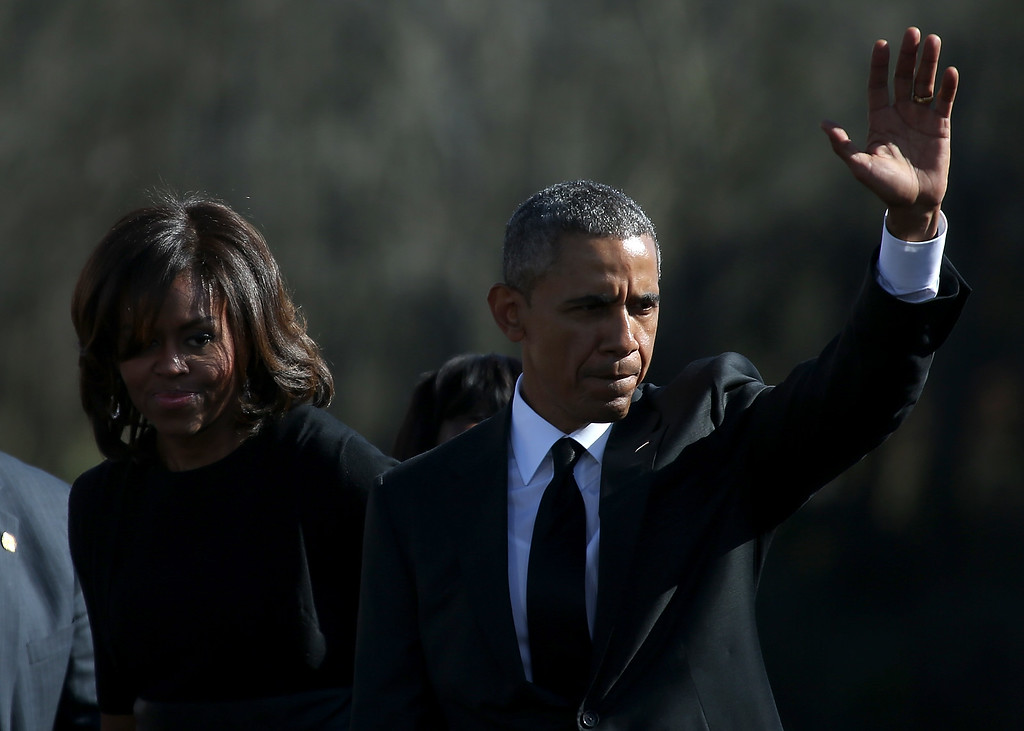 . U.S. President Barack Obama (R) waves with his wife Michelle Obama during a commemoration of the 50th anniversary of the historic civil rights march on March 7, 2015 in Selma, Alabama. Selma is commemorating the 50th anniversary of the famed civil rights march from Selma to Montgomery that resulted in a violent confrontation with Selma police and State Troopers on the Edmund Pettus Bridge on March 7, 1965.  (Photo by Justin Sullivan/Getty Images)