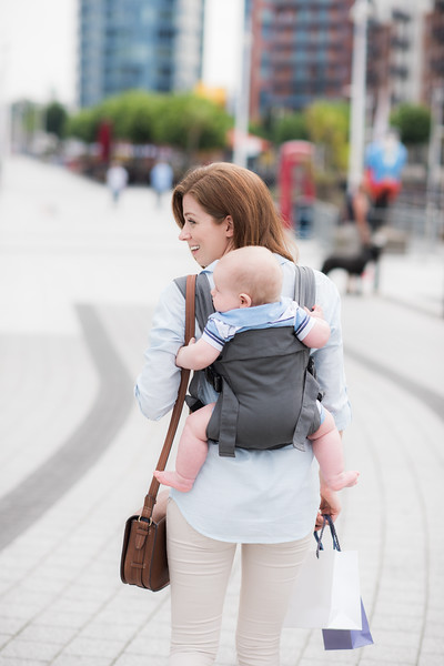 Izmi_Baby_Carrier_Mid_Grey_Lifestyle_Back_Carry_Mum_Walking_In_City.jpg