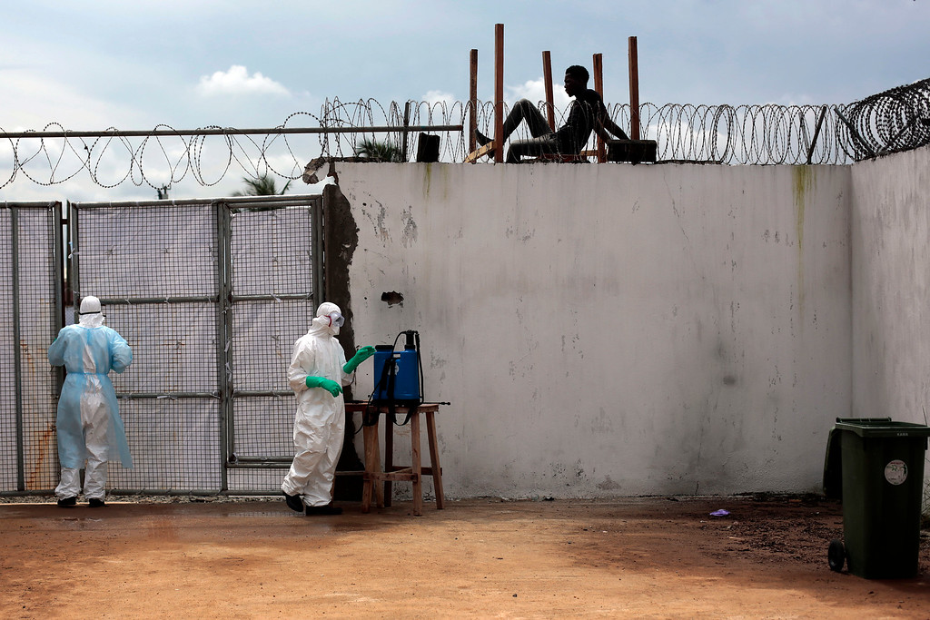 . Health workers stand outside the Island Clinic Ebola isolation and treatment center in Monrovia, Liberia, Friday Sept. 26, 2014.  The outbreak of Ebola has overwhelmed the weak health systems of some of the world\'s poorest countries - there aren\'t enough doctors and nurses or even clinics to treat the spiraling number of cases.(AP Photo/Jerome Delay)