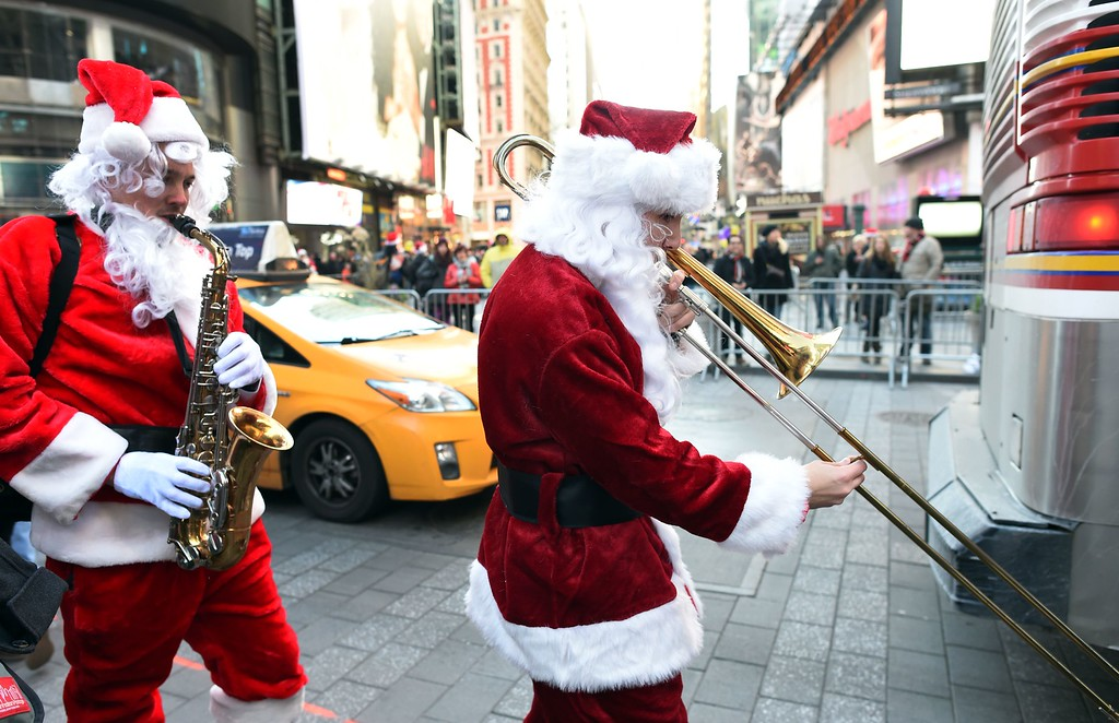 . Santas playing a trombone and sax march though Times Square as hundreds of Santas gather for the annual Santacon festivities on December 13, 2014 in New York. AFP PHOTO/DON  EMMERT/AFP/Getty Images