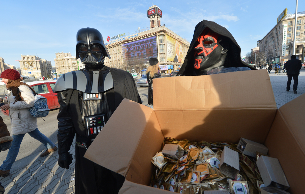 Description of . A leader of the Ukrainian Internet Party, wearing a Darth Vader outfit from the Star Wars saga, and an activist distribute goods on December 20, 2012 on Independence Square in Kiev. The party activists, who traditionally wear Star Wars costumes during their actions, distributed canned foods, matches, condoms, toilet paper, soap, lightbulbs and