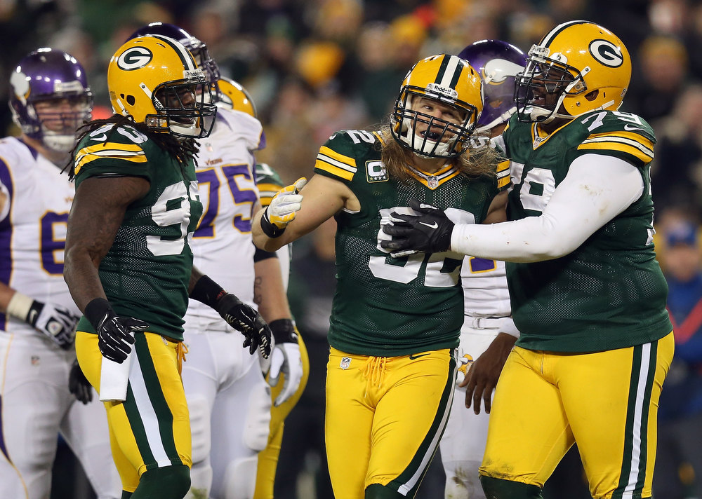 Description of . (C) Linebacker Clay Matthews #52 of the Green Bay Packers celebrates with teammates outside linebacker Erik Walden #93 and defensive end Ryan Pickett #79 after Matthews sacks quarterback Joe Webb #14 of the Minnesota Vikings in the first half during the NFC Wild Card Playoff game at Lambeau Field on January 5, 2013 in Green Bay, Wisconsin.  (Photo by Jonathan Daniel/Getty Images)