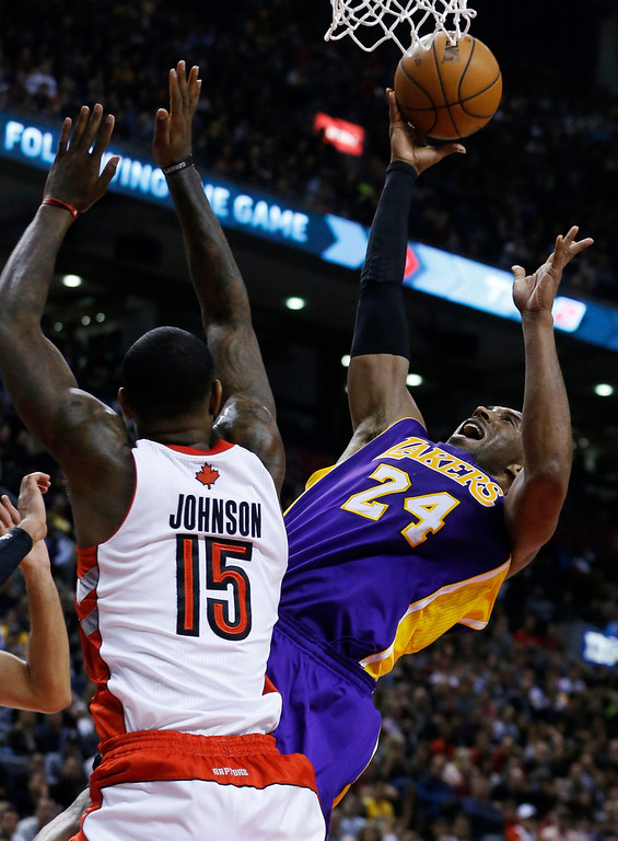 . Los Angeles Lakers\' Kobe Bryant (R) goes the the basket against Toronto Raptors\' Amir Johnson during the second half of their NBA basketball game in Toronto, January 20, 2013.     REUTERS/Mark Blinch