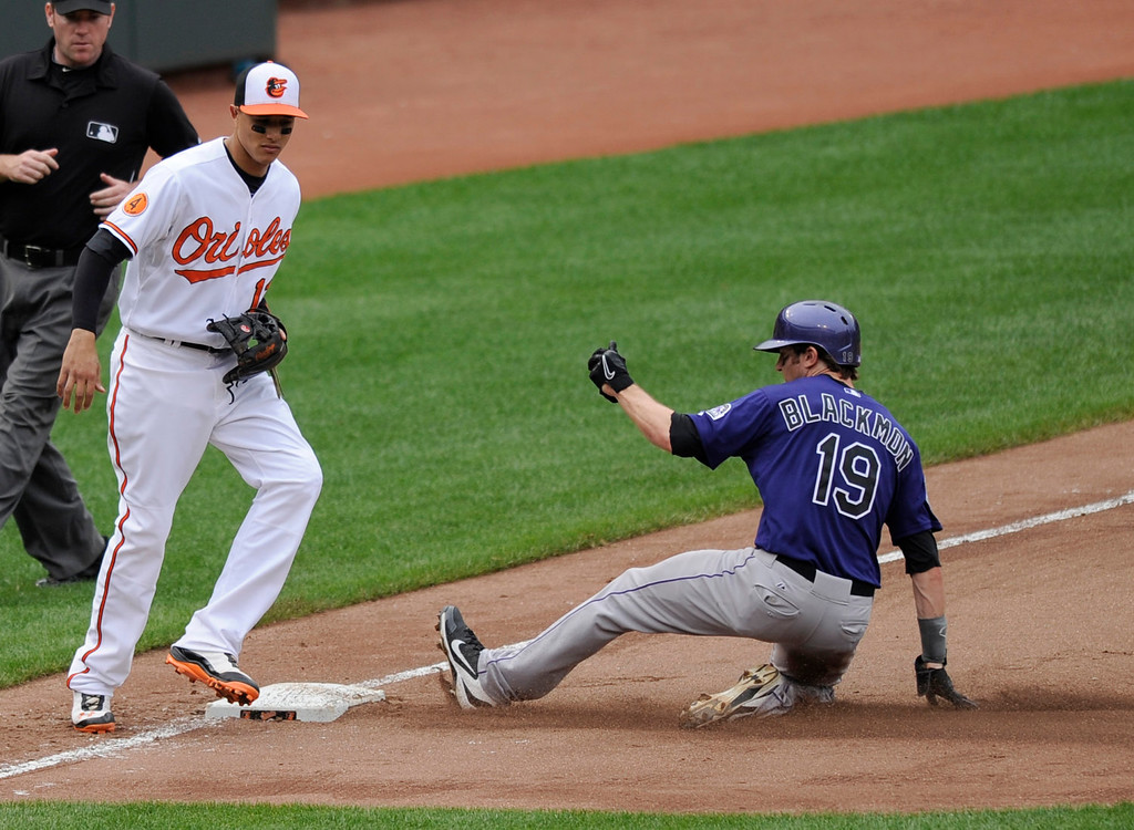 . Colorado Rockies\' Charlie Blackmon (19) steals third against the Baltimore Orioles third baseman Manny Machado, left, during the seventh inning of a baseball game on Sunday, Aug. 18, 2013, in Baltimore. The Orioles won 7-2. (AP Photo/Nick Wass)