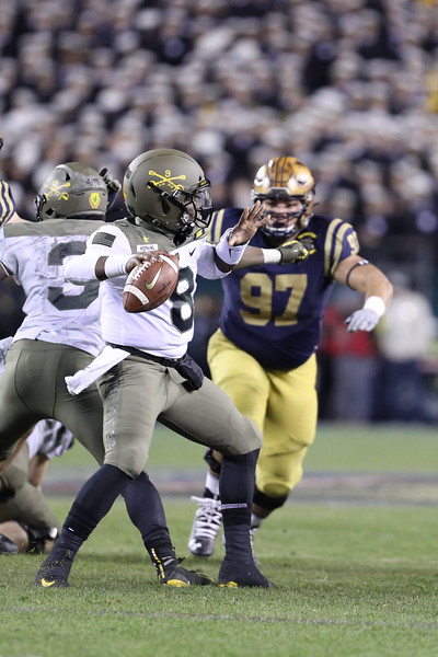 Army quarterback #8 Kelvin Hopkins Jr. drops back to pass under pressure from Navy #97 Dave Tolentino.