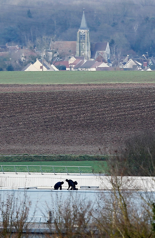 . Armed police officers walk on a roof of a building in Dammartin-en-Goele, northeast of Paris, where the two brothers suspected in a deadly terror attack were cornered, Friday, Jan. 9, 2015. Two sets of attackers seized hostages and locked down hundreds of French security forces around the capital on Friday, sending the city into fear and turmoil for a third day in a series of linked attacks that began with the deadly newspaper terror attack that left 12 people dead. (AP Photo/Michel Spingler)