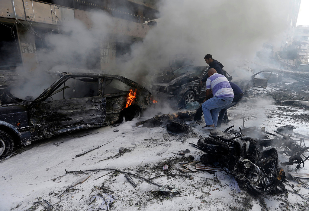 . Two Lebanese men remove a dead body from a burned car, at the scene where two explosions have struck near the Iranian Embassy killing many, in Beirut, Lebanon, Tuesday Nov. 19, 2013.  (AP Photo/Hussein Malla)
