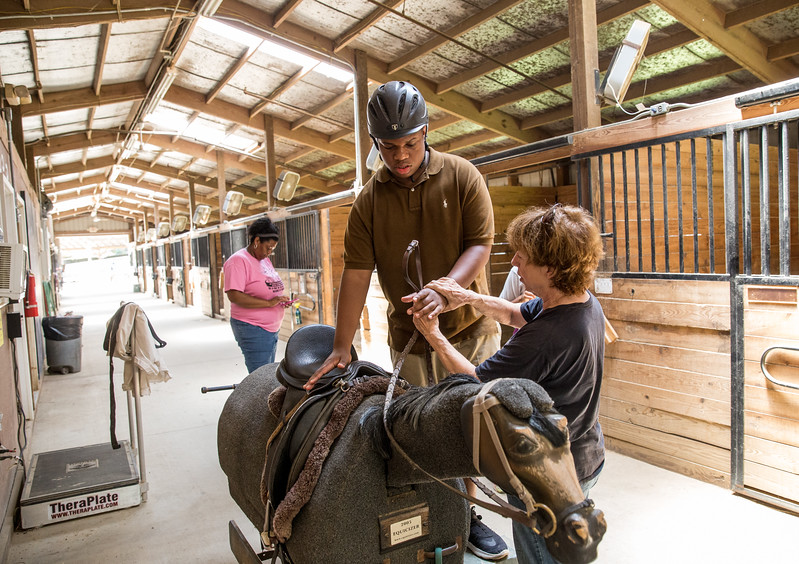 Before heading out to the horse ring, Cameron Scott, 14, visiting with the special needs camp Camp Best Friends, pratices getting on and off a fake horse known as Elvis at the barn.  Chastain Horse Park provides therapeutic programs for special needs campers and for those in need of physical and occupational therapies.  The program is comprised of professional therapist, equestrians and volunteers.    (Jenni Girtman / Atlanta Event Photography)