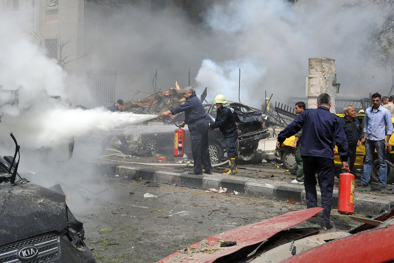 . This photo released by the Syrian official news agency SANA, shows Syrian fire fighters extinguishing burning cars after a huge explosion  shook the Sabaa Bahrat Square, one of the capital\'s biggest roundabouts, in Damascus, Syria, Monday, April. 8, 2013. A car bomb rocked a busy residential and commercial district in central Damascus, killing over a dozen people, wounding at least 50 and causing heavy material damage, a Syrian government official said. (AP Photo/SANA)