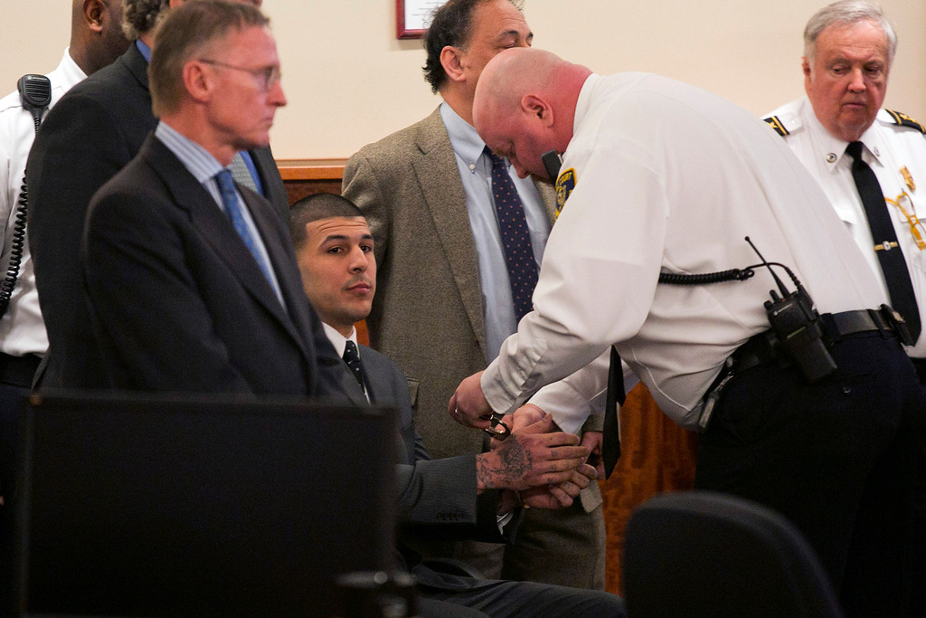 . A court officer places handcuffs on the wrists of former New England Patriots football player Aaron Hernandez after the guilty verdict was read during his murder trial at the Bristol County Superior Court in Fall River, Mass., Wednesday, April 15, 2015.  Hernandez was found guilty of first-degree murder in the shooting death of Odin Lloyd in June 2013.  He faces a mandatory sentence of life in prison without parole.  (Dominick Reuter/Pool Photo via AP)