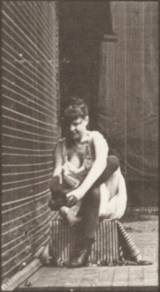 Semi-nude woman putting on boots and rising from a chair