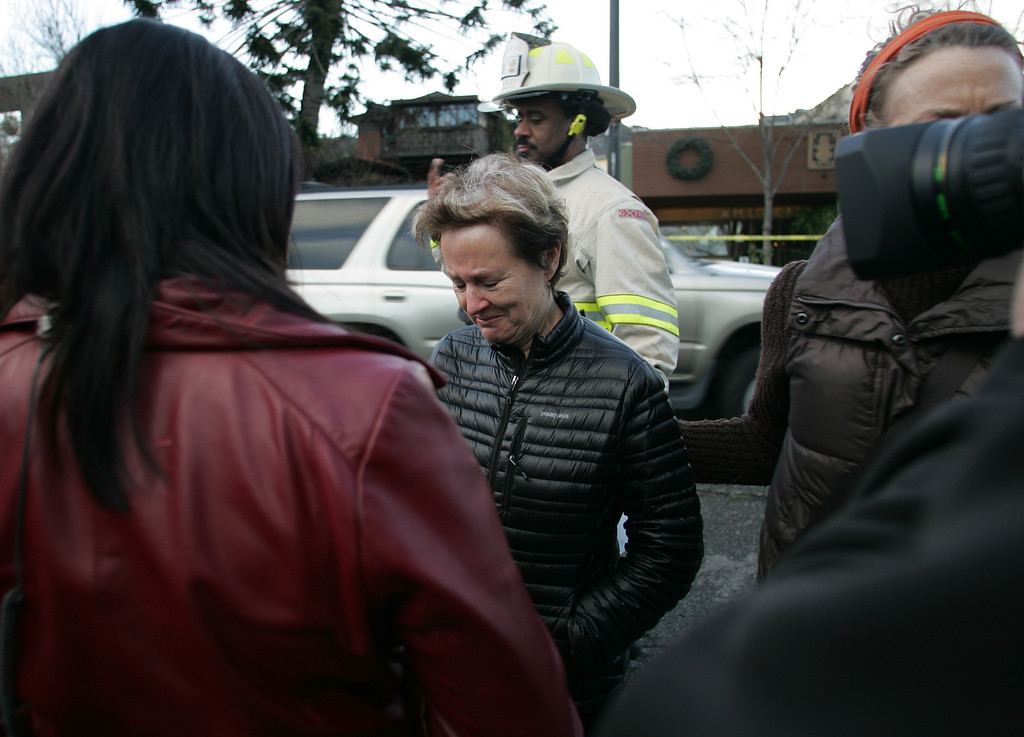 . Alice Waters, center, owner and executive chef of world famous Chez Panisse restaurant in Berkeley fights back tears after taking a tour of her fire damaged restaurant on Friday March 8, 2013. Officials are calling the fire, which started under the front porch at about 3 a.m., suspicious. (Doug Oakley/Staff)