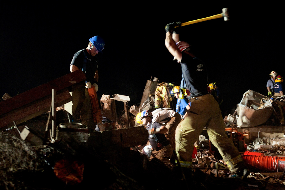 . In this handout provided by the U.S. Department of Defense, two firefighters break through concrete during the search for survivors in the remains of the Plaza Towers Elementary School after it was hit by a tornado on May 20, 2013 in Moore, Oklahoma. The town reported a tornado to be at least EF4 strength and two miles wide that touched down Monday killing at least 24 people and leveling everything in its path. U.S. President Barack Obama promised federal aid to supplement state and local recovery efforts.  (Photo by Maj. Geoff Legler, Oklahoma National Guard Public Affairs/U.S. Department of Defense via Getty Images)