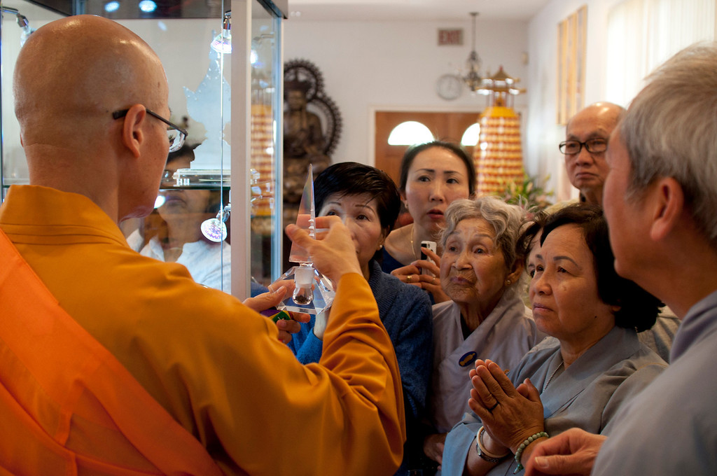 . Dharma Master YongHua shows a crowd hair shariras on display at Lu Mountain Temple in Rosemead, Calif., Sunday, March 31, 2013. Several shariras were made available for viewing to the public including a rare Shakyamuni Buddha tooth relic measuring about two inches in height. (SGVN/Correspondent photo by Anibal Ortiz)