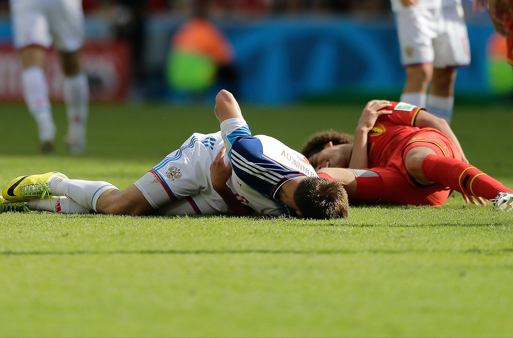. Russia\'s Maksim Kanunnikov, left, and Belgium\'s Axel Witsel lie on the ground after colliding during the group H World Cup soccer match between Belgium and Russia at the Maracana Stadium in Rio de Janeiro, Brazil, Sunday, June 22, 2014. (AP Photo/Bernat Armangue)