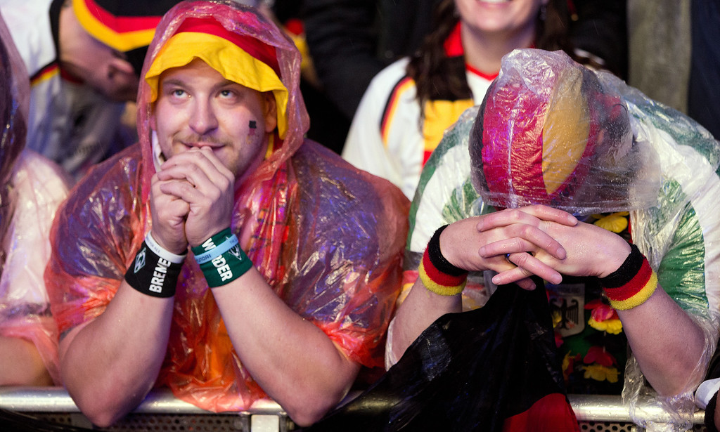 . In this picture made available July 1, 2014 fans watch the FIFA World Cup match Germany vs Algeria at the fan fest at Brandenburg Gate in Berlin, Germany, Monday, June 30, 2014. (AP Photo/dpa, Joerg Carstensen)