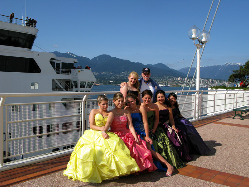 "These seven beauties swarmed down the pier with their digital caneras and ""accosted"", me asking if I'd take their pictures next to the Holland America Veendam.  They are in their high school graduation finery and were attending a soirée at the Vancouver iMax theater on this pier prior to their Prom.  To say the least, I LOVED the attention!!!"