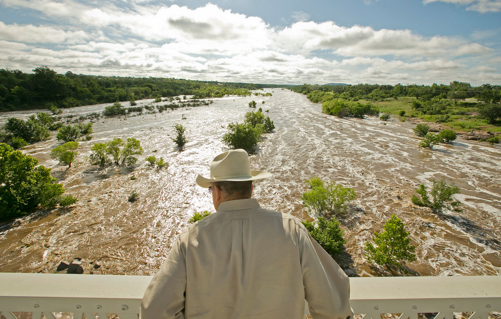 . Tex Toler watches the Llano River rise in Llano, Texas, on Friday, May 29, 2015, after another round of heavy rains. Officials are closely monitoring the levels of rivers in Texas engorged by the deluge of last weekend. (AP Photo/Austin American-Statesman, Jay Janner)