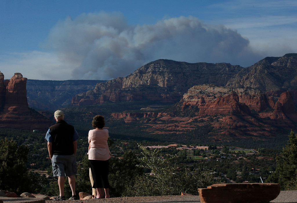 . Tourists watch the Slide Fire from a scenic overlook as it burns up Oak Creek Canyon nearby on Thursday, May 22, 2014, in Sedona, Ariz.  The fire has burned approximately 4,800 acres. (AP Photo/Ross D. Franklin)