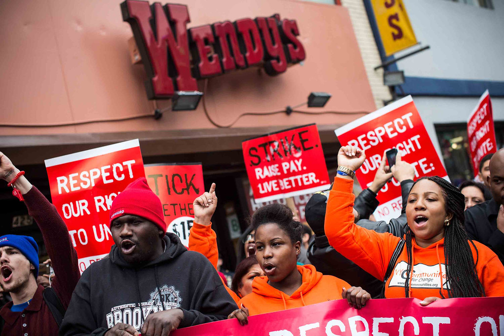 . Protesters rally outside of a Wendy\'s in support of raising fast food wages from $7.25 per hour to $15.00 per hour on December 5, 2013 in the Brooklyn borough of New York City. A growing number of fast food workers in the United States have been staging protests outside restaurants, calling for a raise in wages, claiming it is impossible to live resonably while earning minimum wage.  (Photo by Andrew Burton/Getty Images)
