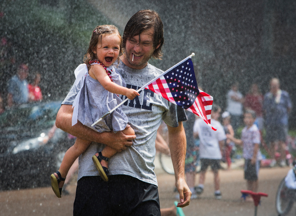 Description of . John David Dowdle holds his 23-month-old Blakely Dowdle as she laughs while being sprayed with water by the Germantown Fire Department during the Poplar Estates Fourth of July parade in Germantown, Tenn., Friday, July 4, 2014. (AP Photo/The Commercial Appeal, Yalonda M. James)