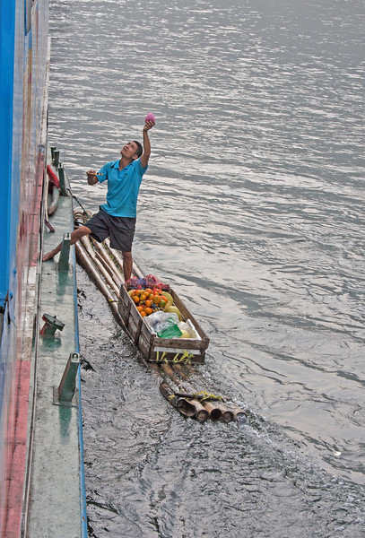 a vendor on a raft selling fruit to passengers on a tour boat, China