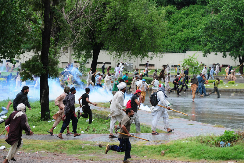. Pakistani opposition protesters run towards police during clashes near the prime minister\'s residence in Islamabad on September 1, 2014. Anti-government protesters armed with rocks and wooden clubs clashed with police in Islamabad on September 1, hours after the powerful army called for a peaceful resolution to the political crisis rocking Pakistan.  ASIF HASSAN/AFP/Getty Images