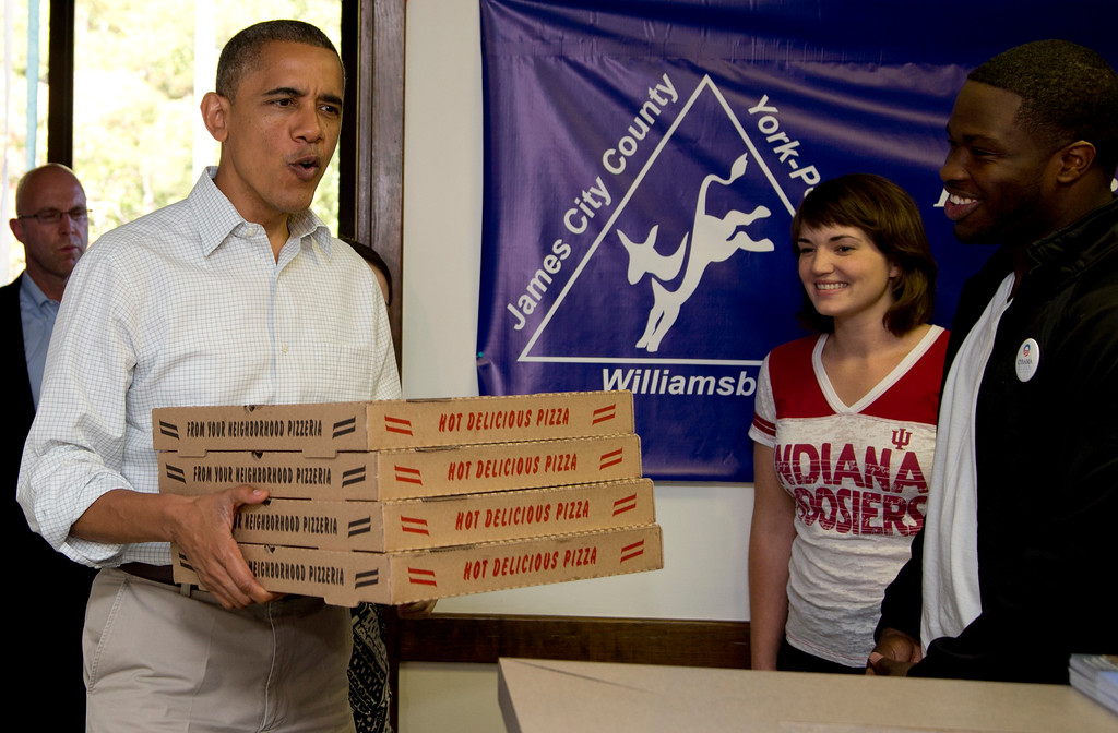 . President Barack Obama arrives with pizza at an Organizing for America field office, Sunday, Oct. 14, 2012, in Williamsburg, Va. (AP Photo/Carolyn Kaster)