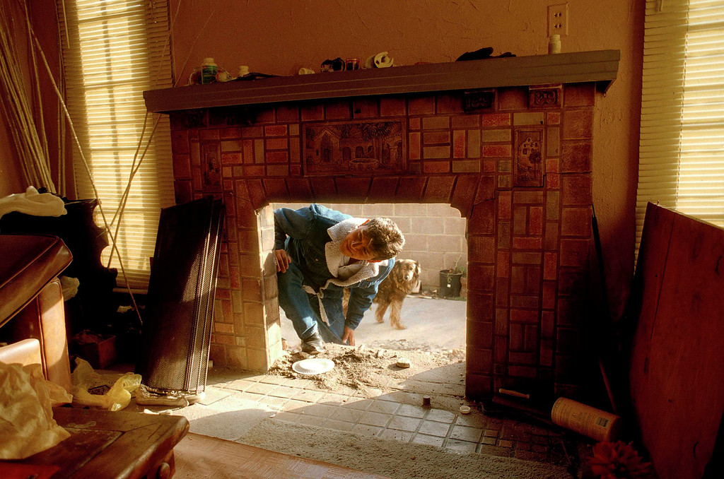 . Abraham Uris, with dog, looks through the fireplace into his home in the Van Nuys section of Los Angeles, Jan. 21, 1994. The chimney was destroyed by Monday\'s earthquake that hit southern California. (AP Photo/John Gaps III)