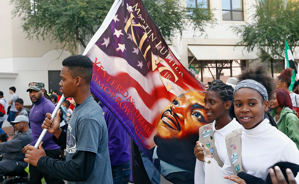 . Participants walk during a Martin Luther King Jr. Day march Monday, Jan. 16, 2017, in Phoenix. (AP Photo/Ross D. Franklin)