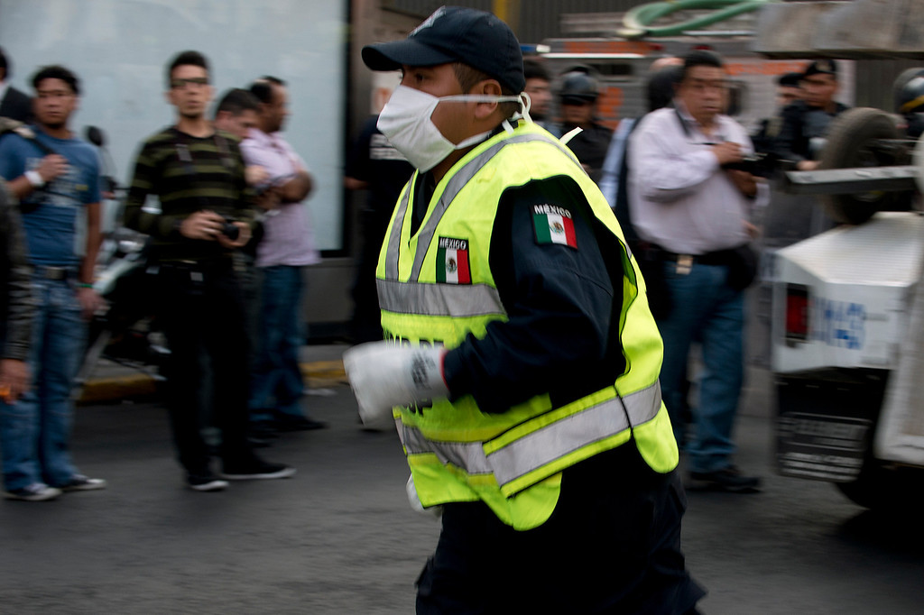 . A paramedic rushes into the skyscraper that houses the headquarters of state-owned Mexican oil giant Pemex, following a blast inside the building in Mexico City on January 31, 2013. An explosion rocked the skyscraper, killing at least 14 people. AFP PHOTO/Yuri CORTEZ