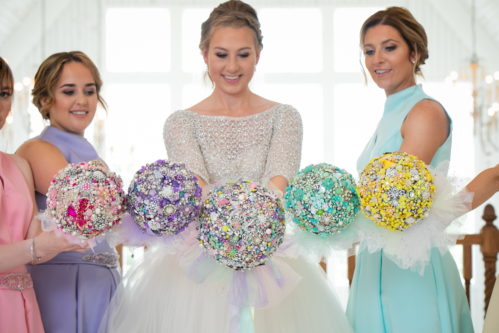 a bride and her bridesmaids holding out their bouquets made of plastic jewelry