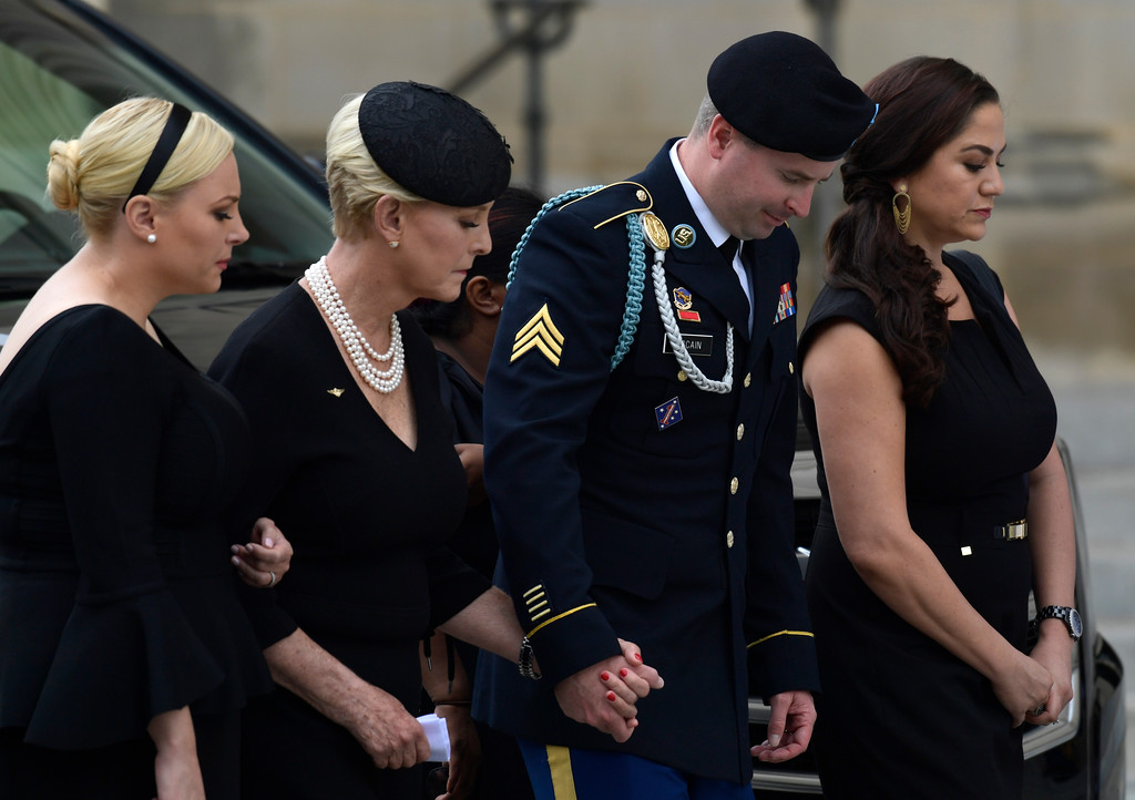 . From left, Meghan McCain, Cindy McCain, Jimmy McCain and his wife Holly pause as they watch the casket of Sen. John McCain, R-Ariz., arrive at the Washington National Cathedral in Washington, Saturday, Sept. 1, 2018, for a memorial service. McCain died Aug. 25 from brain cancer at age 81. (AP Photo/Susan Walsh)
