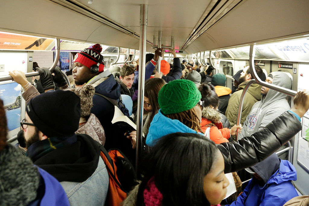 . Commuters crowd an L subway train, Monday, Jan. 25, 2016, in the Brooklyn borough of New York. East Coast residents who made the most of a paralyzing weekend blizzard trudged into the workweek Monday amid slippery roads, spotty transit service and mounds of snow that buried cars and blocked sidewalk entrances. (AP Photo/Mark Lennihan)