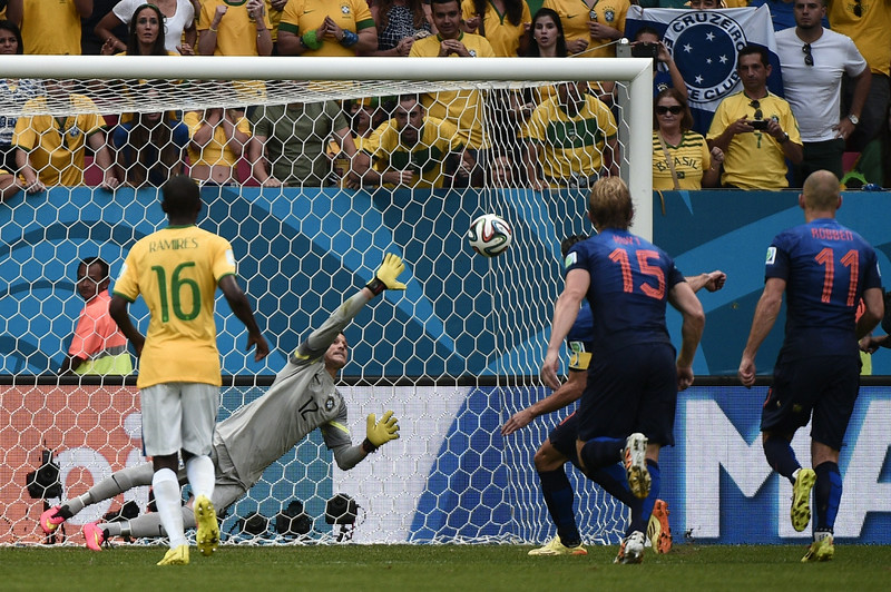 . Brazil\'s goalkeeper Julio Cesar (R) fails to save Netherlands\' forward and captain Robin van Persie\'s penalty during the third place play-off football match between Brazil and Netherlands during the 2014 FIFA World Cup at the National Stadium in Brasilia on July 12, 2014. (DAMIEN MEYER/AFP/Getty Images)