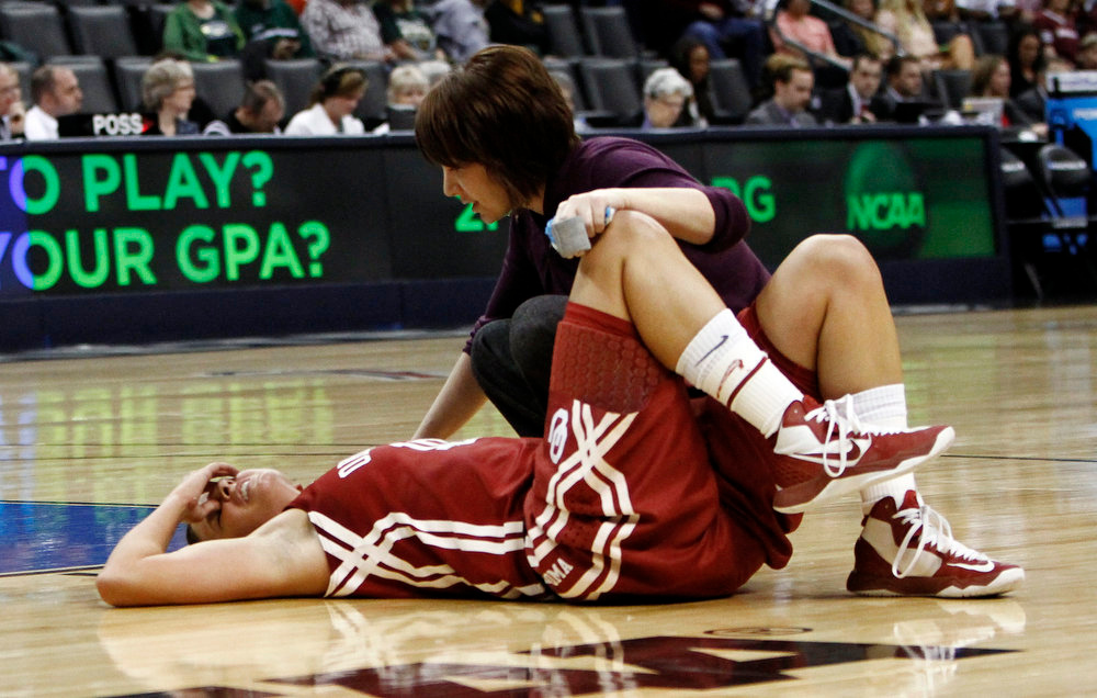 Description of . Oklahoma's guard Morgan Hook is tended to by a trainer after getting hit during a drive against Tennessee during the regional semifinal in the women's NCAA college basketball tournament in Oklahoma City, Sunday, March 31, 2013. (AP Photo/Alonzo Adams)