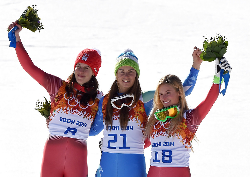 . (L-R) Gold medalist Dominique Gisin of Switzerland, gold medalist Tina Maze of Slovenia and bronze medalist Lara Gut of Switzerland celebrate on the podium during the flower ceremony for during the Alpine Skiing Women\'s Downhill on day 5 of the Sochi 2014 Winter Olympics at Rosa Khutor Alpine Center on February 12, 2014 in Sochi, Russia.  (Photo by Pascal Le Segretain/Getty Images)
