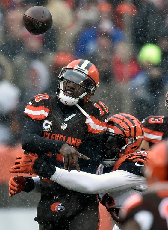 . Cleveland Browns quarterback Robert Griffin III (10) is hit as he throws an incomplete pass in the first half of an NFL football game against the Cincinnati Bengals, Sunday, Dec. 11, 2016, in Cleveland. (AP Photo/David Richard)