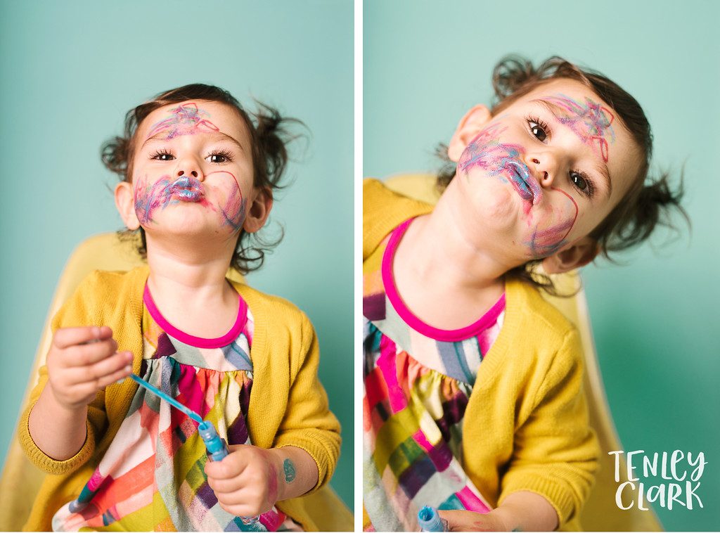 Playful studio portraits of toddler doing her own makeup on colorful backdrops. Commercial photography by Tenley Clark.