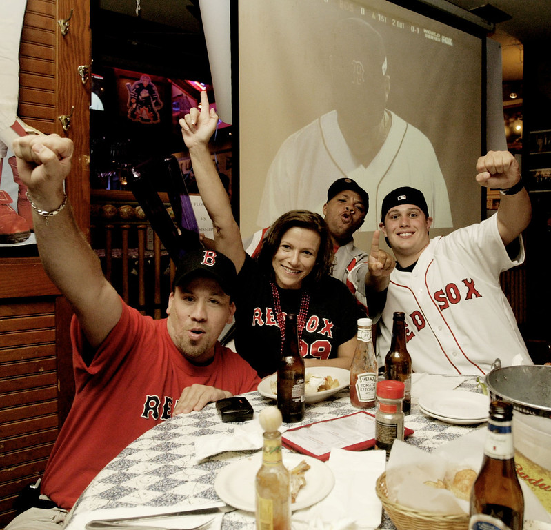 . Boston Red Sox baseball fans, from left to right, Chris Sprague and his wife Linda Sprague, of St. Louis, Quan Zilla, of New York, and Ryan Mahoney of Boston whoop it up at Ozzie\'s Resturant and Sports Bar in Maryland Heights, Mo.,  while watching the Boston Red Sox, St. Louis Cardinals World Series baseball game Sunday, Oct. 24, 2004. The bar is owned by former St. Louis Cardinals shortstop and Hall of Famer Ozzie Smith. The four were the only Red Sox fans in the bar. (A Photo/James A. Finley)