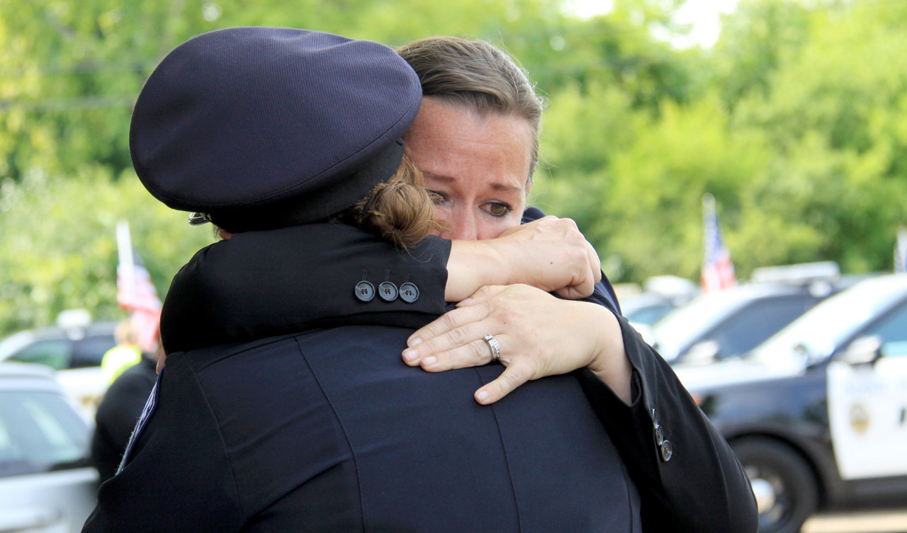 . Officers hug outside St. Stephen\'s Lutheran church following the funeral service for Mendota Heights police officer Scott Patrick on Wednesday. (Minnesota Department of Public Safety Pool Photo: Jen Longaecker)