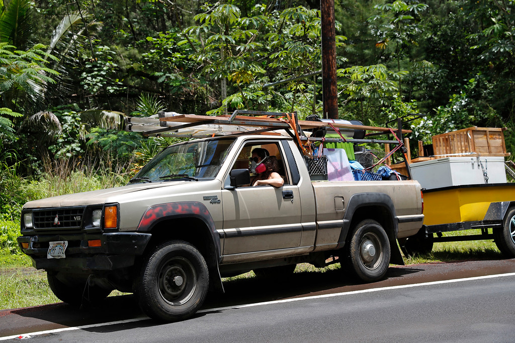 . While wearing an air filter mask, Laura Dawn drives her truck loaded with her possessions as she and her husband flee the lava eruption, Sunday, May 6, 2018, near Pahoa, HI. Their property is just below the active lava eruption and they fear their land will get covered in lava. They are moving further upcoast to a safer area. (AP Photo/Marco Garcia)
