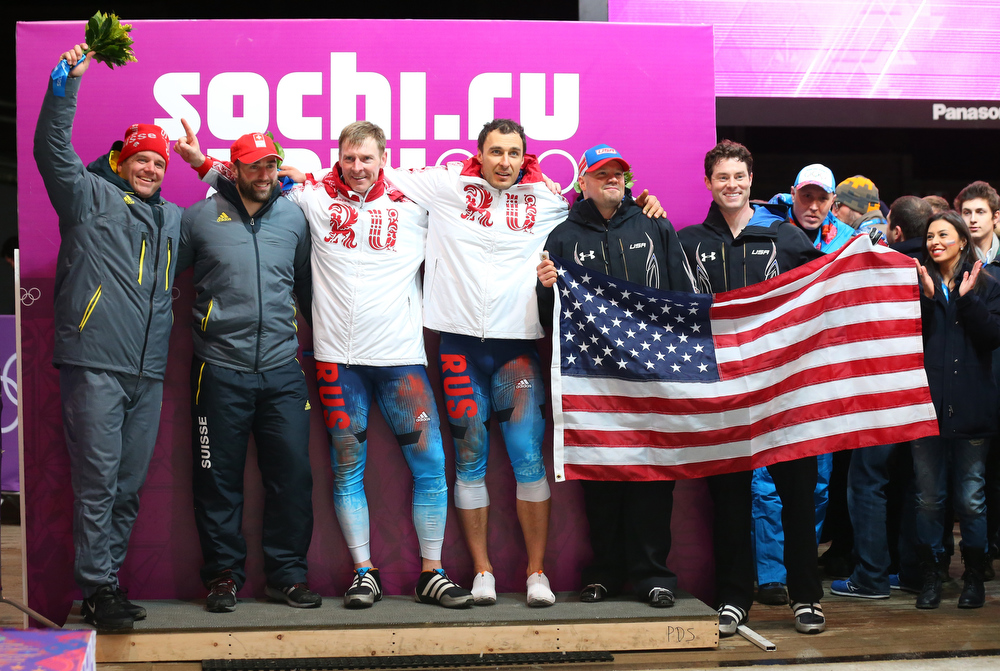 . Silver medalists Beat Hefti and Alex Baumann of Switzerland team 1, gold medalists Alexander Zubkov and Alexey Voevoda of Russia team 1 and bronze medalists Steven Holcomb and Steven Langton of the United States team 1 celebrate during the flower ceremony for the Men\'s Two-Man Bobsleigh on Day 10 of the Sochi 2014 Winter Olympics at Sliding Center Sanki on February 17, 2014 in Sochi, Russia.  (Photo by Alex Livesey/Getty Images)