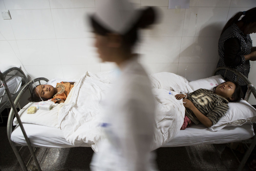 . This picture taken on August 3, 2014 shows a nurse (C) walking past two injured children in a hospital corridor during the first night after a 6.1 magnitude earthquake hit Ludian county in Zhaotong, in southwest China\'s Yunnan province.  More than 367 people died and nearly 2,000 were injured when a strong earthquake hit southwest China\'s mountainous Yunnan province on August 3, bringing homes crashing to the ground and sparking a massive relief operation.    AFP PHOTOSTR/AFP/Getty Images