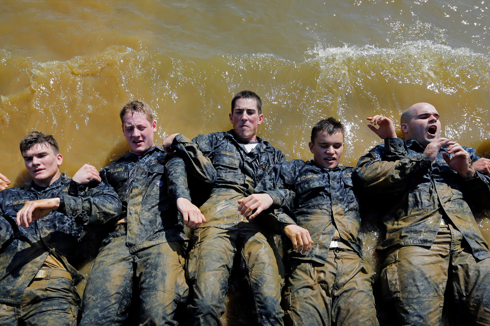 """. Freshman midshipmen, known as \""""plebes,\"""" perform sit ups on the banks of the Severn River during Sea Trials, a day of physical and mental challenges that caps off the freshman year at the U.S. Naval Academy in Annapolis, Md., Tuesday, May 13, 2014. (AP Photo/Patrick Semansky)"""