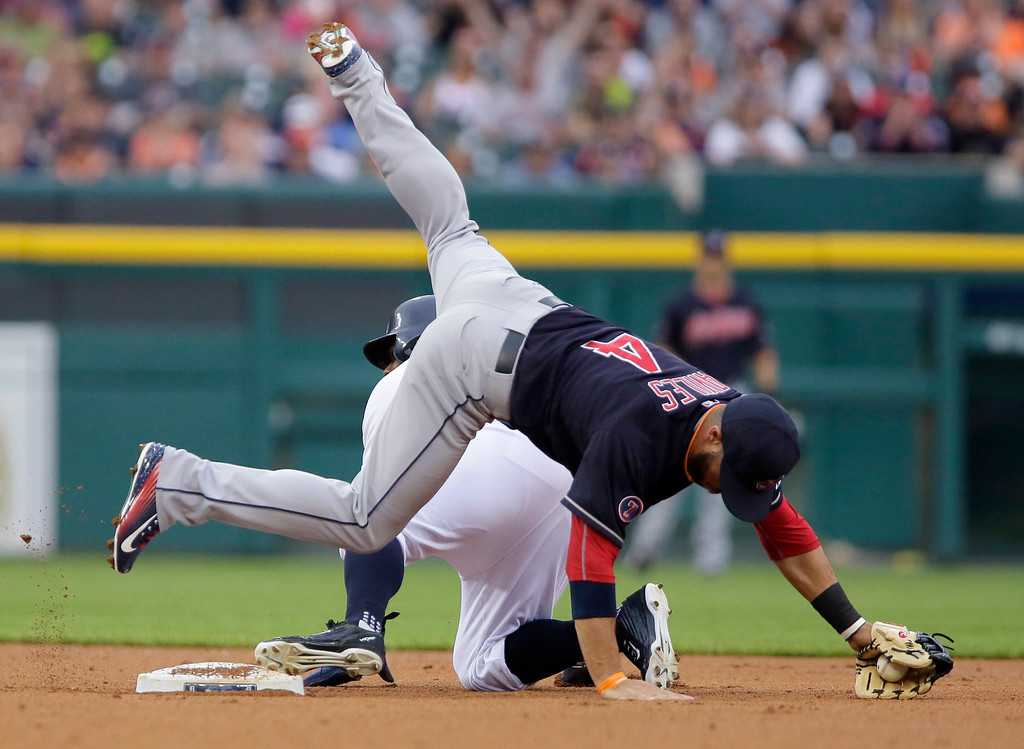 . Cleveland Indians shortstop Mike Aviles (4) tumbles over Detroit Tigers\' Rajai Davis after failing to make the tag for a stolen base during the first inning of a baseball game Friday, June 12, 2015, in Detroit. (AP Photo/Duane Burleson)