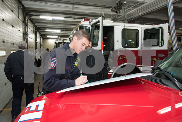 11/20/17 Wesley Bunnell | Staff New Britain Fire Department Local 992 raised $18,648.80 during their Fill the Boot 2017 campaign which concluded with a check presentation to the Muscular Dystrophy Association on Monday afternoon at New Britain Fire Headquarters on Beaver St. Firefighter Matt Abdifar who acted as the coordinator for the drive signs the ceremonial check on the hood of a fire department vehicle.