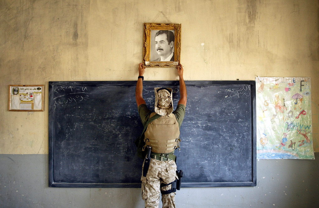 . A U.S. Marine pulls down a picture of Saddam Hussein at a school April 16, 2003 in Al-Kut, Iraq. A combination team of Marines, Army and Special Forces went to schools and other facilities in Al-Kut looking for weapons caches and unexploded bombs in preparation for removing and neutralizing them. (Photo by Chris Hondros/Getty Images)